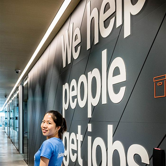 Woman poses in front of We help people get jobs sign