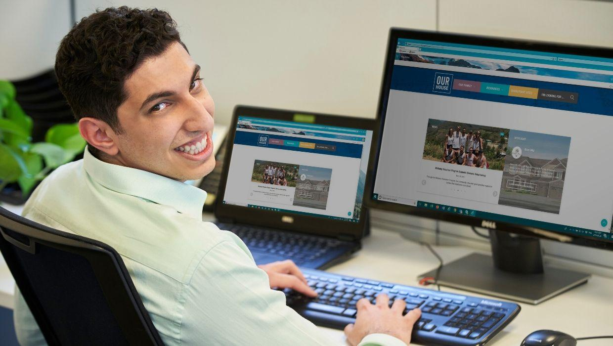 Young man working on computer, smiling at camera