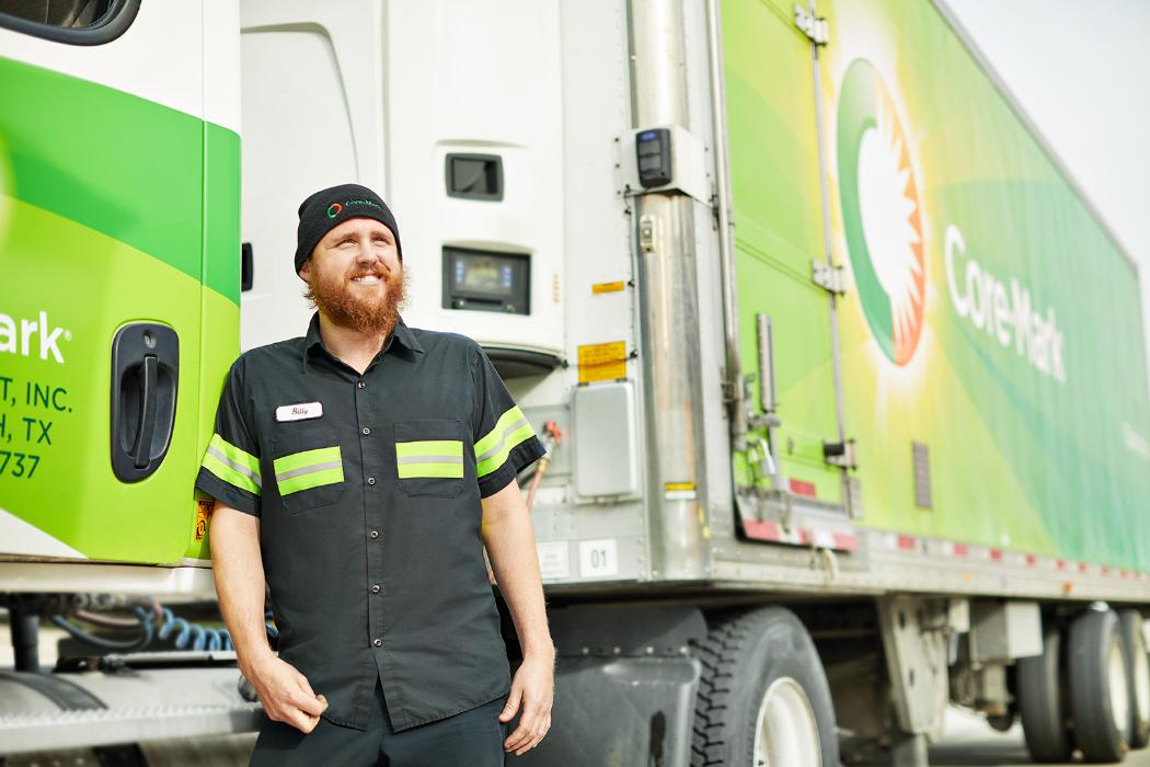 Local driving careers at Core-Mark. A Core-Mark driver leans against a truck.
