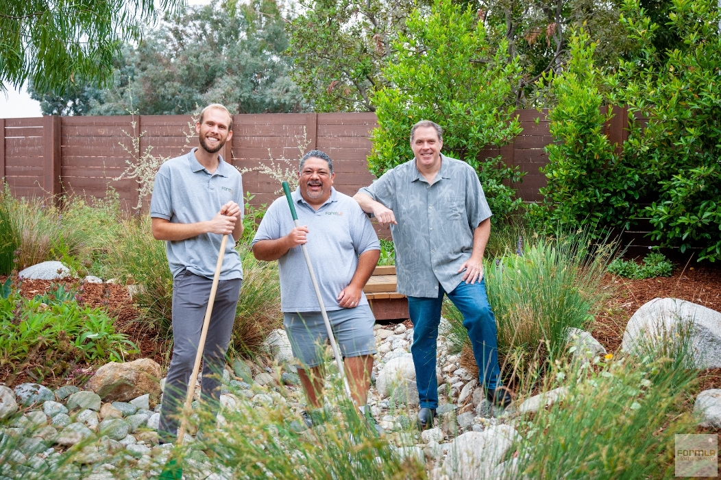 Maintenance care managers and a landscape architect on a bridge in a FormLA Landscaping garden.