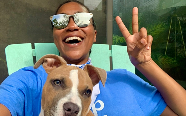 Indeedian poses with dog giving peace sign
