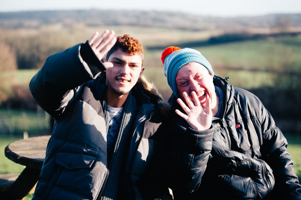 two service users enjoying the winter countryside while waving