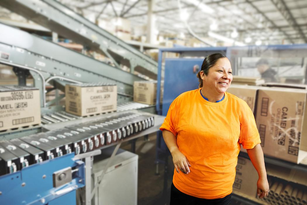 Warehouse careers at Core-Mark. A female employee in a warehouse smiles happily.