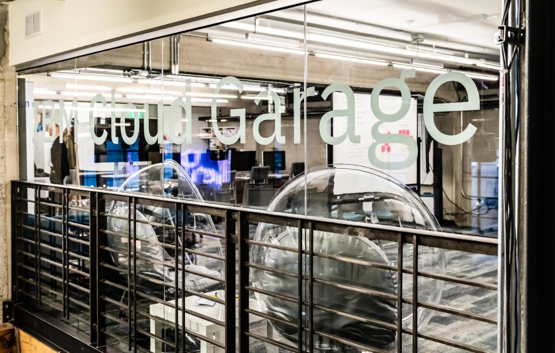 Modern office with a sign on the glass wall that says IBM Cloud Garage