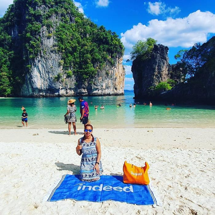 Woman poses on Indeed-branded towel in tropical location