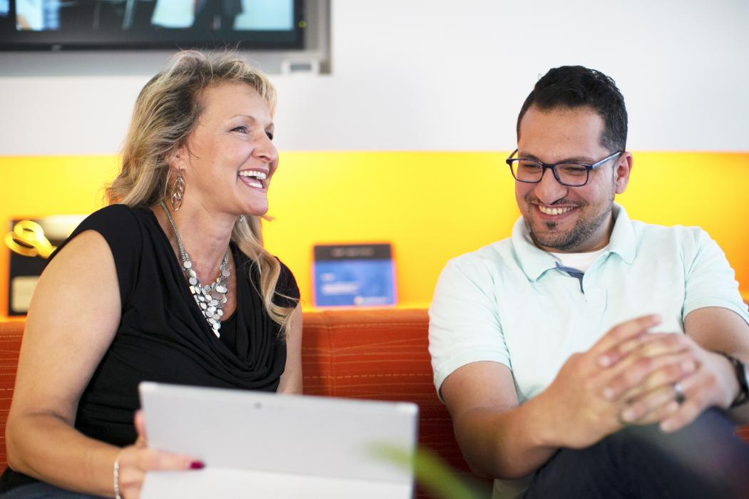Left: a woman laughing and holding a laptop Right: a man smiling and looking at the laptop