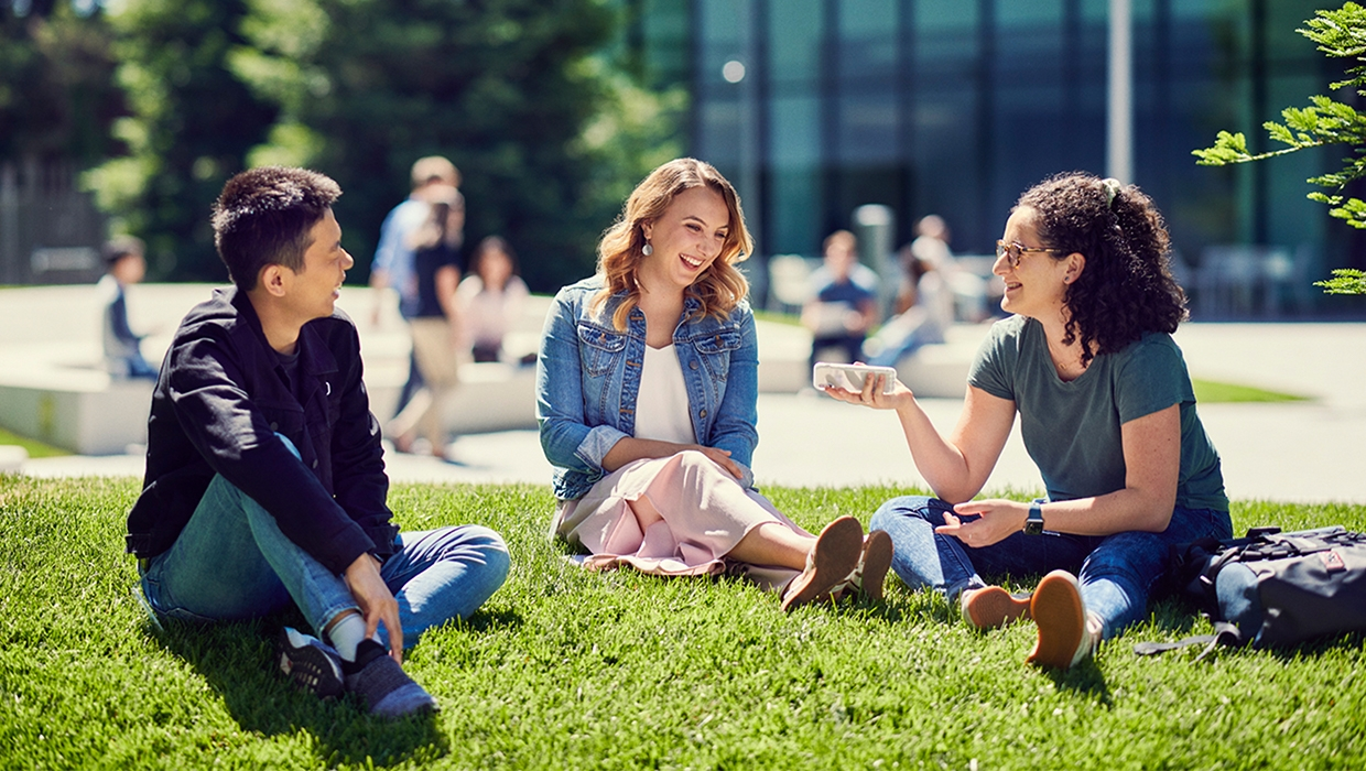 Image of students sitting on the grass having a conversation.