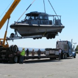 Loading harbor patrol boat onto trailer for transport.