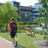 A student strolls near the pond in front of the Oceanography and Physics Building.