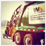 photo of Waste Management, A helper operating safely on the back of a residential truck in Southeast Texas