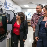 Employees check out the progress of their 3-D printed product in the Adaptive Tech center.