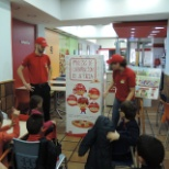 Telepizza workers explaining the process of making the pizza.