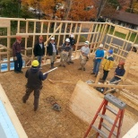 Team frames a house with a Habitat For Humanity Supervisor and volunteers