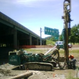 Drilling 60ft holes to make micropiles for highway foundation