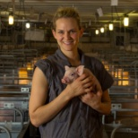 This herdsperson is taking a break in the farrowing barn to share the pride she takes in her piglets