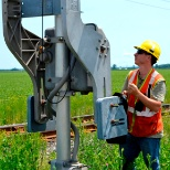 RailTerm employee performing maintenance on railway signal and communications equipment.